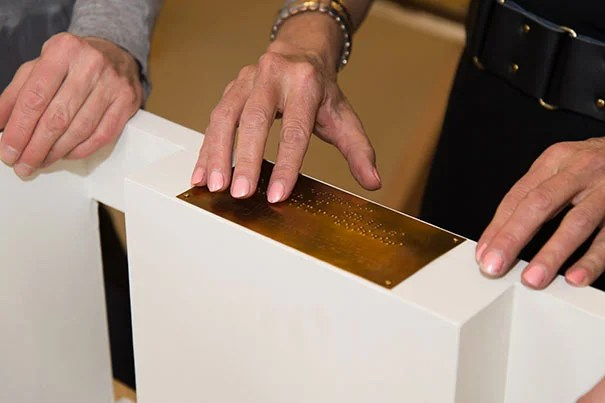 Nina Livingstone, who is blind, reads the Braille plaque that accompanies the exhibit models. Kevin Grady/Radcliffe Institute