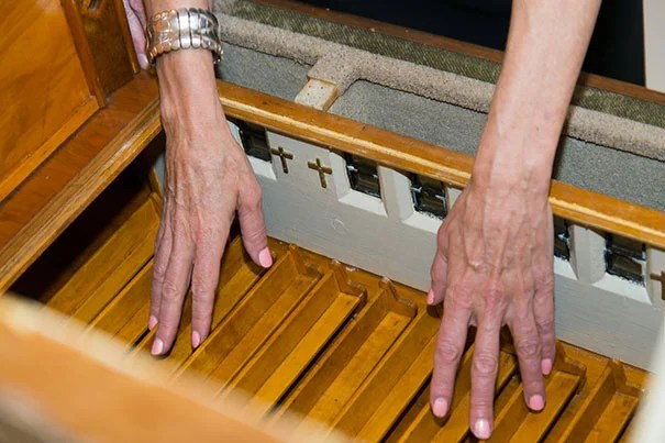 Wendy Jacob wants visitors to place touch on equal footing with sight. Livingstone examines the church pews on a two-floor church model. Kevin Grady/Radcliffe Institute