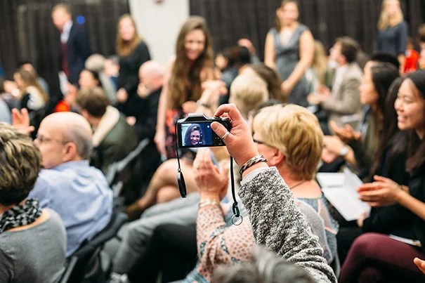 A proud family member snaps a photo as graduates stand to be recognized at the Midyear Graduates Recognition Ceremony on December 2, 2016. Photo by Will Halsey