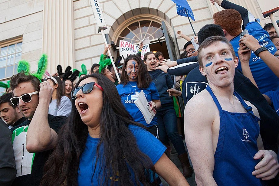 House representatives, including Gia Marciano '18 (left) from Quincy House,  and Tom Culp '19 from Lowell House, charge down the steps of University Hall with their letters for freshmen. Jon Chase/Harvard Staff Photographer