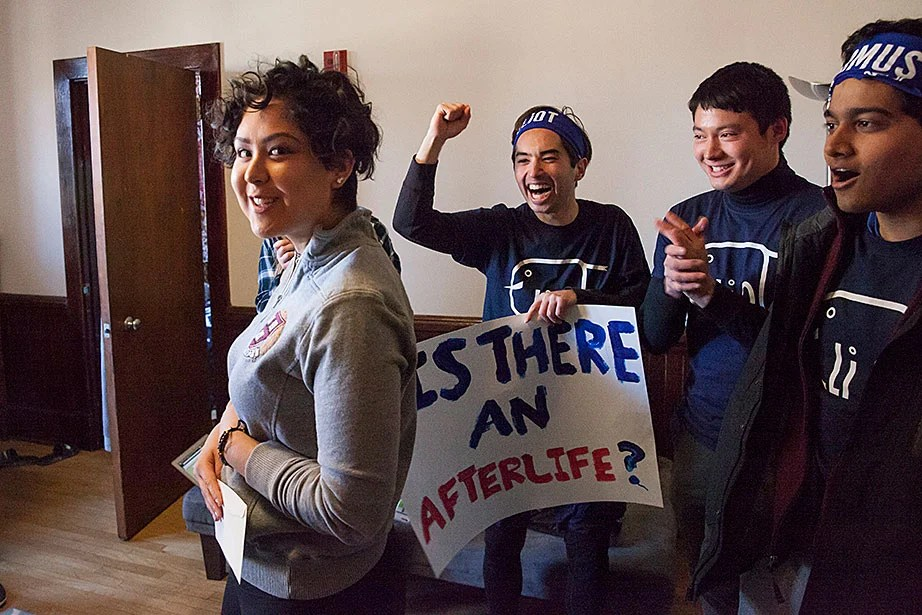 Kim Arango '20 stands in Matthews Hall with her letter from Eliot House, while House members whoop it up in the background. Jon Chase/Harvard Staff Photographer