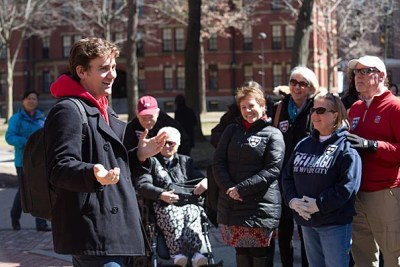 Bennett Capozzi '17 leads a campus tour in Harvard Yard as his mother (center) looks on admiringly. A dedicated altruist, he has volunteered at a Greek refugee camp and with Boston Foods, a group on campus working to combat food scarcity in metro Boston.