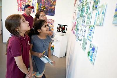 Gardner Pilot Academy third-graders Sophia Deoliveira (left) and Mariaeliza Vasquez and Vasquez's parents look for the girls' artwork on display at the Harvard Ed Portal.