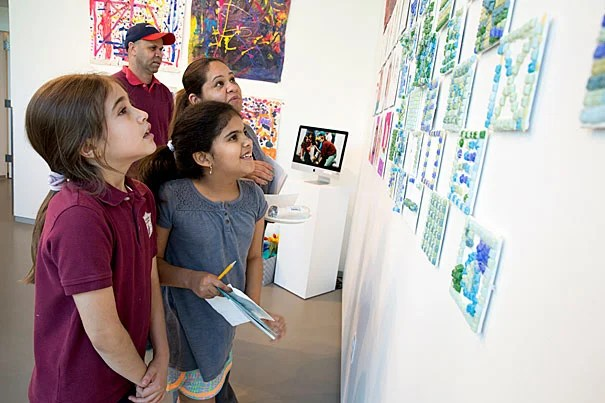 Gardner Pilot Academy third-graders Sophia Deoliveira (left) and Mariaeliza Vasquez and Vasquez's parents look for the girls' artwork on display at the Harvard Ed Portal.