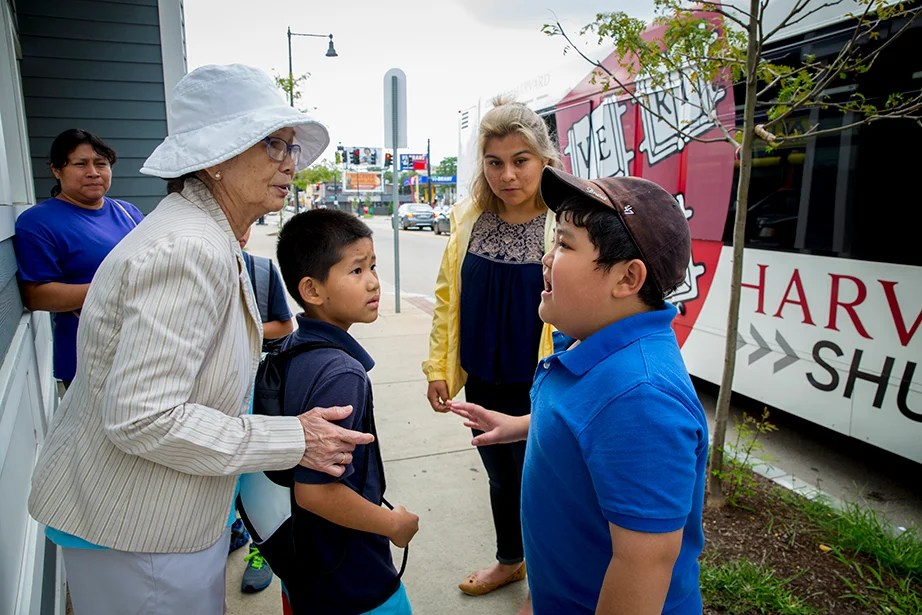 At the bus stop, Kevin Nguyen translates information about the BRYE program for Khang Nguyen's grandmother.