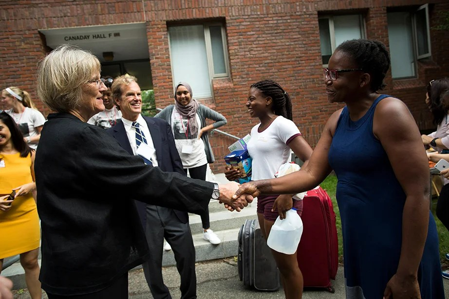 President Faust (from left) and Dean of Freshmen Tom Dingman meet with students and families, including Ruva Chigwedere '21 and her mother Lorine, from Florham Park, N.J., in front of Canaday Hall. Stephanie Mitchell/Harvard Staff Photographer