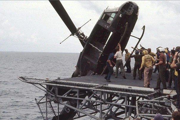 Crew members aboard the USS Okinawa push a South Vietnamese helicopter overboard to make room for incoming flights filled with evacuees Saigon fleeing the Vietcong.