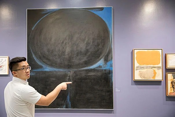 This untitled piece from 1963 contains large geometric forms of black paint edged by a vibrant blue. Justin Wong, program assistant for the Fairbank Center for Chinese Studies, views the work at the CGIS exhibit.
