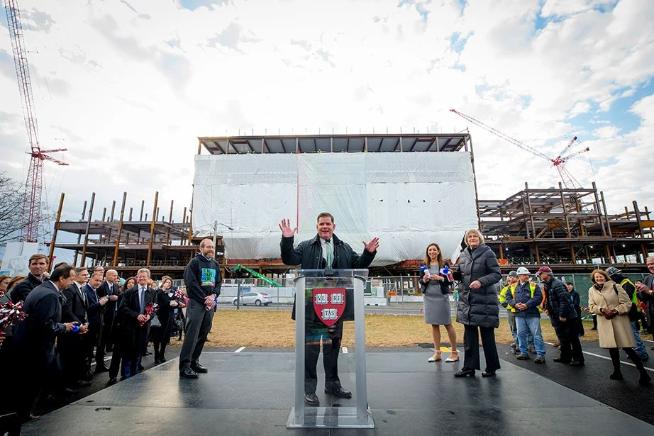 Harvard Provost Alan Garber, Mayor Martin J. Walsh, and President Drew Faust prepare to give the signal to raise the final beam of the Science and Engineering Complex in Allston.