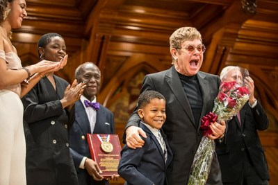 Chase Sullivan, 8, presents Sir Elton John with flowers at Monday's ceremony held at Sanders Theatre.