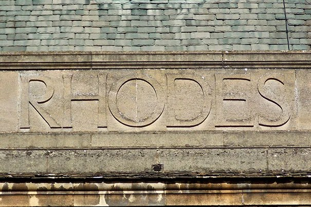 The photo of the embossed stone sign that reads Rhodes was taken at the back of the Rhodes House, the headquarters of the Rhodes Scholarships and the Rhodes Trust.