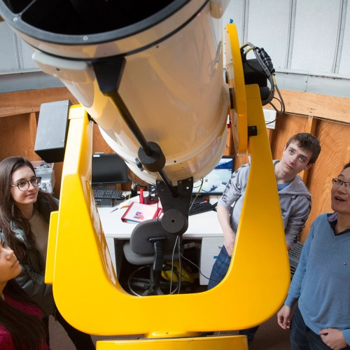 "CRLS students Sophia Sonnert (from left), Tatiana Athanasopoulos, and Jonas Hansen meet with Harvard postdoc George Zhou at the Clay Telescope at the Science Center. Zhou is a mentor in the Science Research Mentoring Program at the CfA. The program pairs high school students with ""real-live"" scientists to study space."