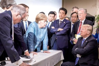 Angela Merkel, surrounded by world leaders at G& summit in 2018, leans over table to face Donald Trump, whose arms are folded.
