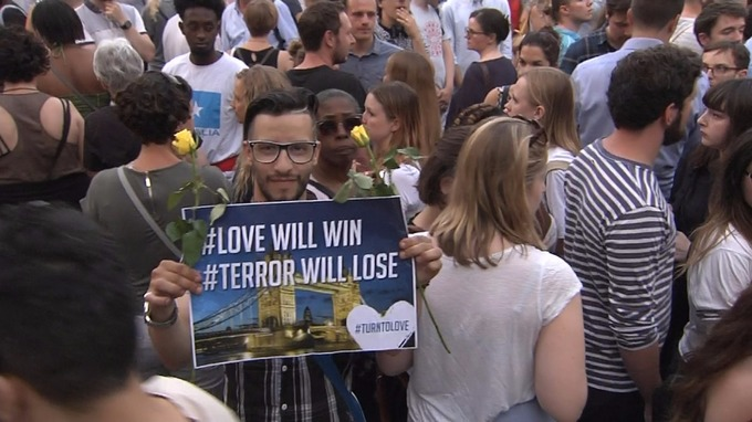 A man holds a 'love will win, terror will lose' poster.