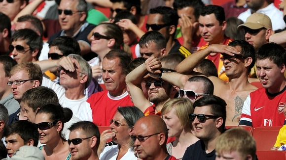 A packed stand at the Emirates Stadium as football fans enjoy the game in the sun.