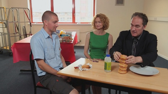 3 people look at 5 doughnuts on a table