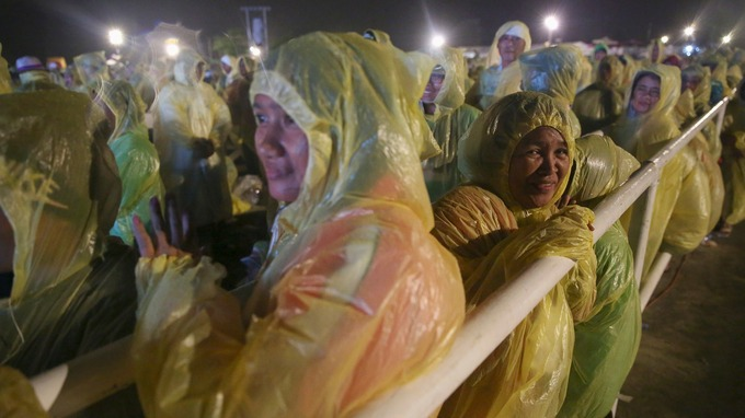 Pilgrims brave rain and strong wind as they wait at Tacloban airport.