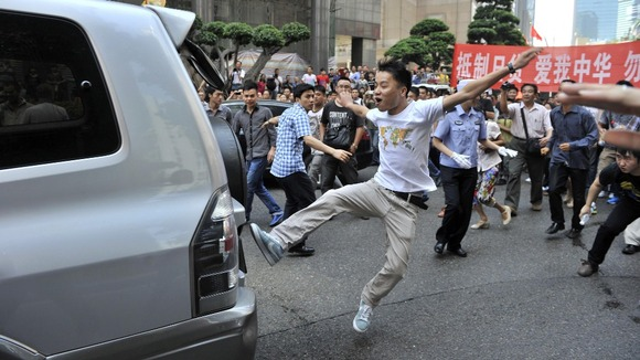 A demonstrator kicks a Japanese-brand car during a protest in Chongqing