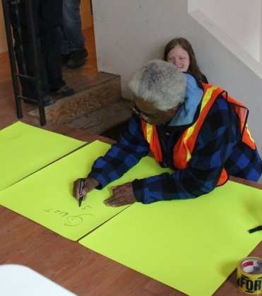 Robinson makes a sign in support of Pierce resident Kristie Allbrandt who was facing an eviction following a foreclosure.