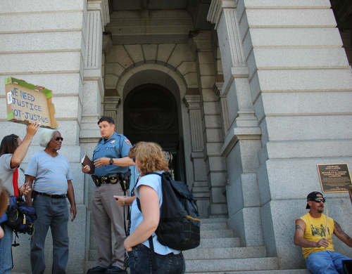 """Virgil Robinson (2nd from left) speaks to officer on June 19, 2015 after being approached several times. Supporters say that it was due to the presence of supporters that security later backed off from asking him to leave. He told officers, """"I have a right to be here and am not leaving."""""""
