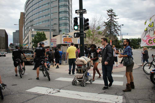 Two protesters run in front of a police cruiser that had accelerated to a high rate of speed against a red light.  The men on the right of the stroller then stood between the mother and baby and the police cruiser to block it from moving into the intersection.  The men then accompanied the mother and baby to safety across the street.