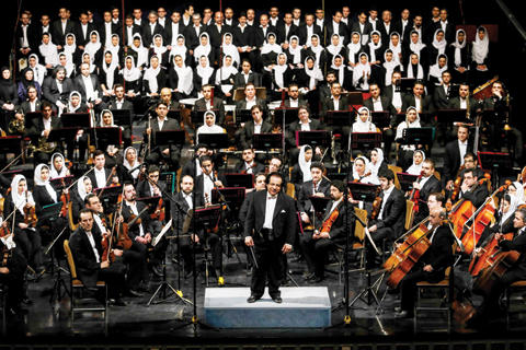 A file picture taken on March 16, 2015 shows Iranian conductor Ali Rahbari (center) and the Tehran Symphony Orchestra greeted by the audience after performing at the Vahdat Hall in Tehran.-AFP