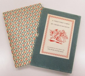 The cover and box of a 1940 edition of A Christmas Carol. The cover is cloth with a Christmas themed pattern and the case has a white and red illustration of people dancing.