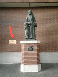 Image shows the brass book drop embedded in wall behind the Louise de Marillac sculpture on the quad side of the John T. Richardson Library.