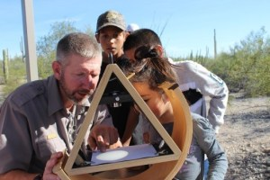 Children and a park ranger look at a large spot of light in a triangular wooden structure.