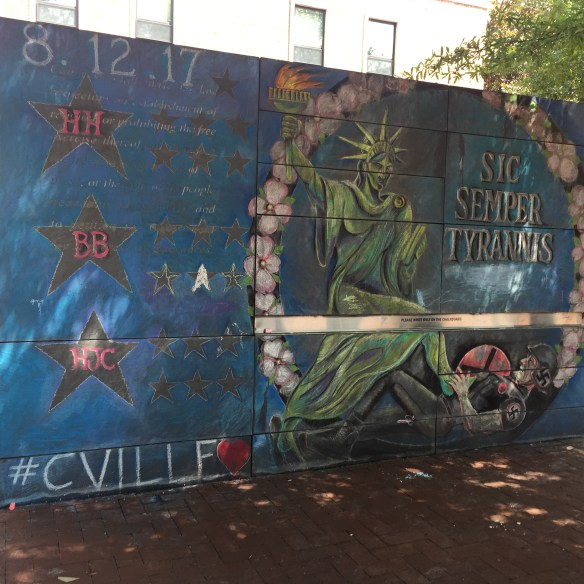 """This mural appeared on the downtown mall's Freedom of Speech wall following the events on August 12, 2017. It depicts: the initials of the three individuals who died on August 12 (Heather Heyer and Virginia State Police officers Lt. H. Jay Cullen and Trooper Berke M.M. Bates) and the Statue of Liberty vanquishing a Nazi alongside the Virginia state motto, """"Sic Semper Tyrannis."""""""