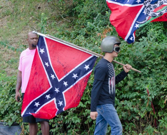 """Photo by Gary Powell titled """"McIntire Street."""" An African American man looks on as a white man carrying a Confederate flag walks past"""