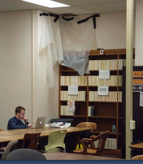 A student studies at a dark table underneath a section of wall held together with plastic and messy black tape
