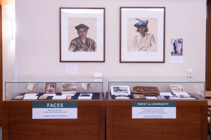 An exhibit with two large framed drawings on the wall and two cases full of memorabilia