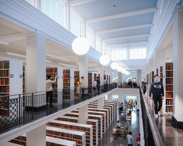 A view over the railing from the upper level of an area filled with book shelves and study spaces. There is natural light coming from above and people are utilizing the space.