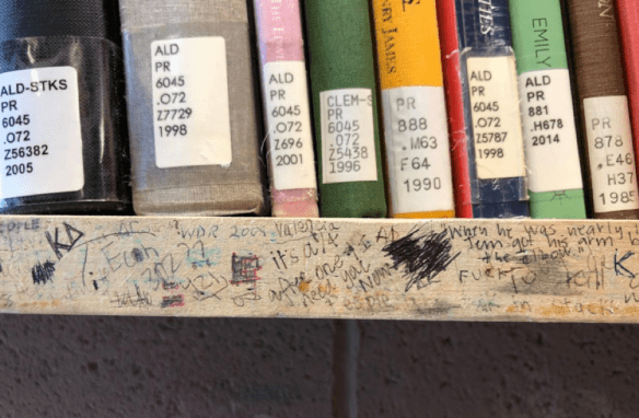 A wooden shelf thick with scribbled writing