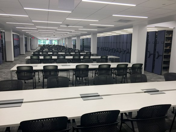 View of table, chairs, and compact shelving on 1st floor of Clemons Library