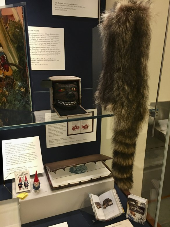 """Display case featuring a raccoon skin, a fierce hound's face (the biding for a book about Conan Doyle's Holmes story """"The Hound of the Baskervilles""""), and a leather book edged with shark teeth."""""""