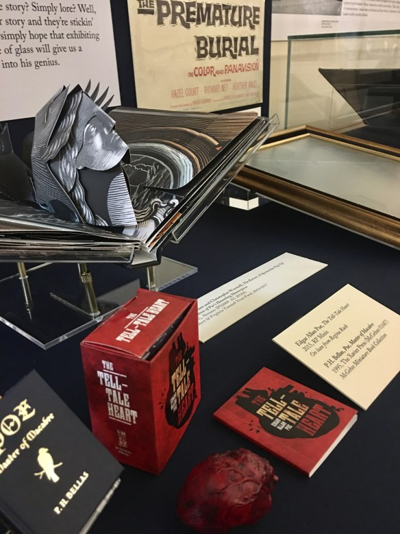 "Display case of Poe items in the exhibition: a pop-up book of Poe's The Raven and miniature book of his story ""The Tell-Tale Heart."""