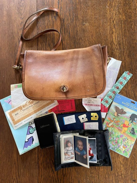 The brown leather Coach bag pictured from above with the contents — wallet, photos, checkbook, address book, Easter cards, ticket stubs, receipts — spread out around it