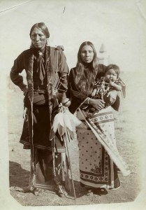 A husband and wife in traditional Native dress stand for their portrait. The man holds a feathered ceremonial rattle, and the woman her infant child.