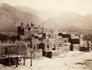 Tiered, square buildings and access ladders of an adobe village in full sun with mountains in the background.