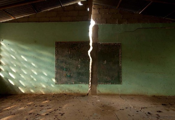 A green-tinted wall is cracked down the center, showing light coming through in the shape of lightening