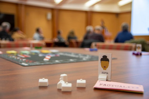 An avatar (a card with the picture of person, upright in a holder) with the name Sofia written under the picture, along with several pieces that players collect, and the Factuality gameboard in the background.