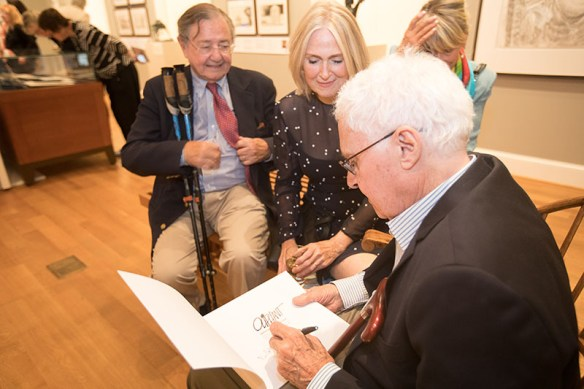 A seated Pat Oliphant at a reception in the exhibition gallery autographs an exhibition catalog for a man and woman who look on, smiling.