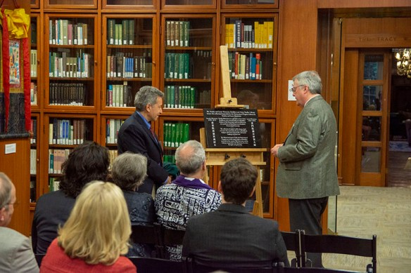 University Librarian John Unsworth before an audience of attendees, with the collection on glassed-in book shelves in the background, views a plaque on an easel.