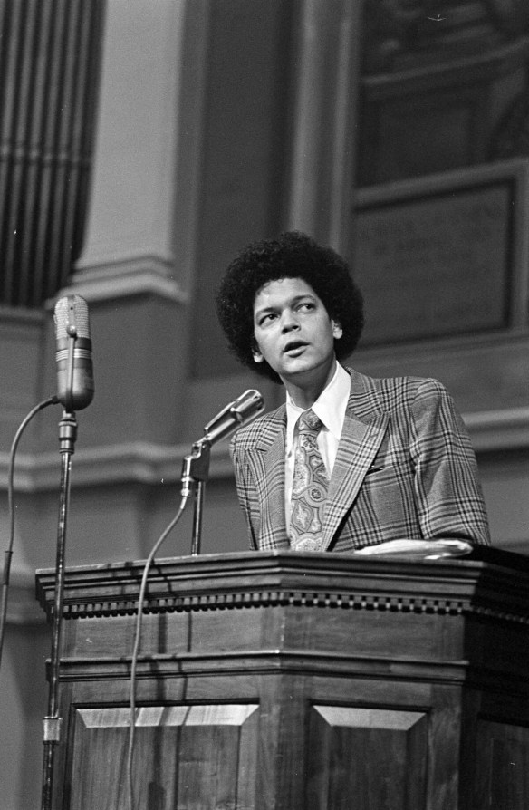A young Julian Bond, with afro and suit and tie, stands behind a podium, speaking