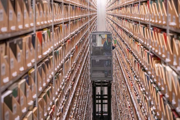 Ivy Stacks worker on a lift (called an order-picker) handling books high up between rows of shelves in the Ivy Stacks storage and retrieval facility.