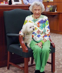Ann Lee Brown sitting in a chair smiling, her while, curly-haired dog, Nikki-Beau, sitting beside her.