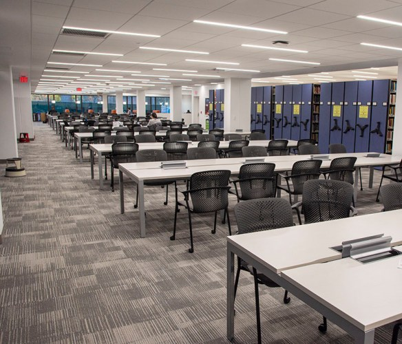 View of the new tables, chairs, carpet, and light fixtures in Clemons 1st floor study space beside the mobile shelving units.