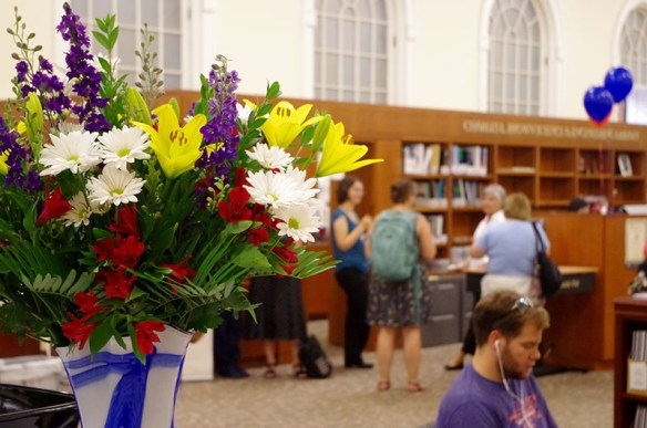 In the foreground of the main service area of the Brown Science & Engineering Library there is a vase of cheerful, multi-colored flowers, while in the background a student studies at a laptop with ear phones, and staff conduct business at the service desk.